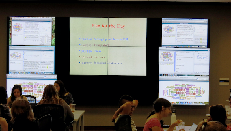 A class working by the display wall, where multiple laptop screen are displayed